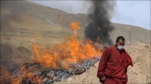 Monje budista ante la cremación de las víctimas