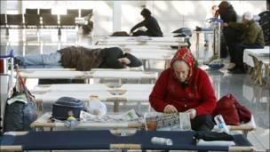 Mujer mayor leyendo el periódico en el aeropuerto