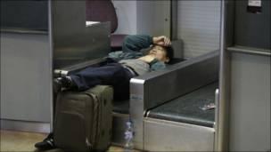 Pasajero durmiendo en la cinta transportadora de un mostrador