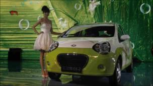 Modelo posando con un Geely Panda, un coche electrico