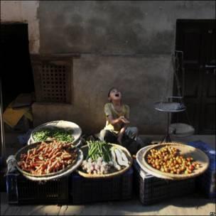Una niña nepalí juega delante de su puesto de verduras.
