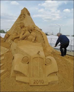 """Работник выставки ухаживает за скульптурой из песка """"Отечественный кинематограф"""""""
