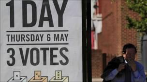 Un hombre camina al lado de un anuncio electoral.