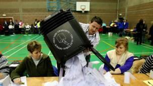 Un hombre vacía una urna al término de las votaciones.