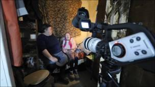 Пожилая женщина сидит на кровати. В кадре видеокамера. Фотография desper_i