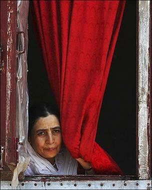 Mujer asomada a una ventana en Srinagar, India
