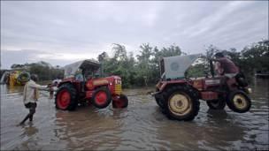 Tractores en aldea inundada en Ongle, India
