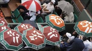 Personas con paraguas en Roland Garros