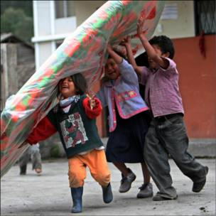 Niños juegan durante su traslado a un albergue en Cotalo