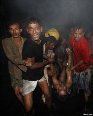 Жители Дакки выносят пострадавшего из пожара