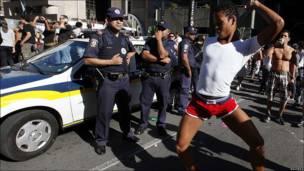 Un joven baila delante de policías