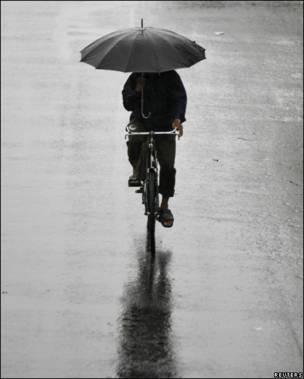 Hombre en bicicleta con paraguas