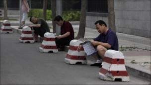 Padres chinos aguardan sentados en la calle exámenes escolares