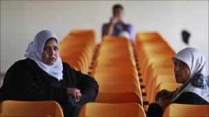 Mujeres palestinas esperan a cruzar la frontera de la Franja de Gaza con Egipto