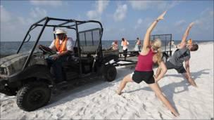 Practicantes de Yoga en una playa de Alabama mientras empleados de BP limpian restos del derrame de crudo