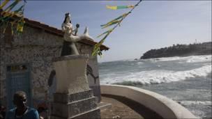 Hombre frente a estatua de Yemanyá en Salvador, Brasil
