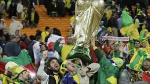 Aficionados de Brasil con una Copa gigante.