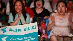 Dos surcoreanas animan a Corea del Norte.