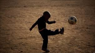 Un niño juega al fútbol en Sudáfrica.