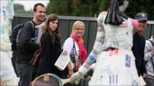 Espectadores miran a una estatua hecha con material reciclado.