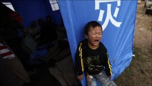 Niño llora frente a tienda de campaña en Fuzhou, China