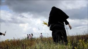 Monja ortodoxa lleva flores tras una ceremonia.