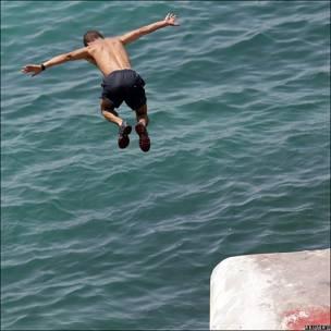Niño saltando al mar