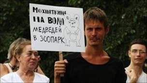 """Человек с плакатом """"Мохнаткина - на волю, медведей - в зоопарк"""""""
