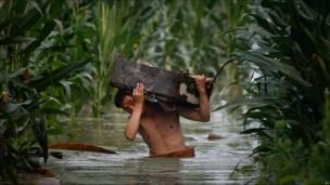 Hombre carga sus pertenencias en zona inundada en provincia china de Jilin