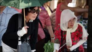 Туристы из Японии спасаются от московской жары под зонтиками