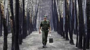 Солдат с лопатой в лесу