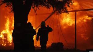 Пожарные на фоне огня
