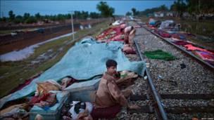 Chico sentado al costado de la vía del tren en la localidad de Pabi junto a todas las pertenencias de su familia