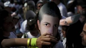 Chica llevando una máscara con la cara del soldado Gilad Shalit en una manifestación frente a la residencia del primer ministro israelí
