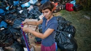 Девушка складывает одежду в мешки