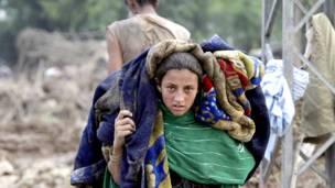 شابة تحمل ما تبقى من متاعها بعدما دمرت الفيضانات بيتها في نوشير