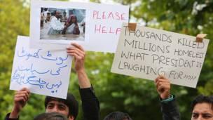 """ورفع متظاهرون اخرون لافتات كتب عليها """"الاف الاشخاص يموتون، الرئيس في عطلة""""، و""""الاف القتلى، ملايين المشردين، ما الذي يضحك الرئيس؟"""""""