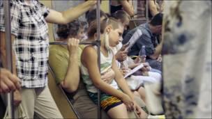 Мальчик на коленях у женщины в маске в метро