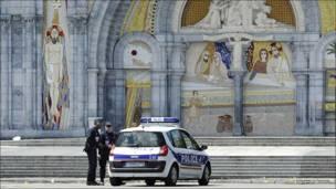 Dos policías y un coche policial frente al santuario de Lourdes.