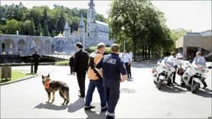 Personal de seguridad, policías y un perro en el santuario de Lourdes