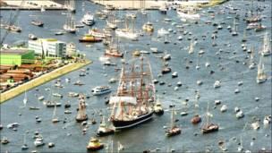 Un barco alto escoltado por decenas de pequeños.