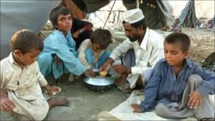 Familia paquistaní compartiendo un plato de arroz.