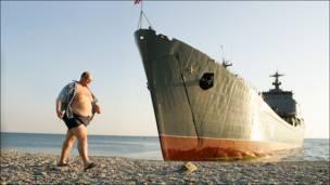 Человек на пляже и военный корабль