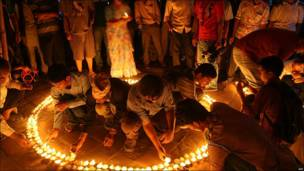 Personas en un círculo, encendiendo velas.