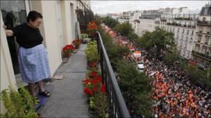 Una mujer observa desde el balcón de su casa, en París, el paso de una de las manifestaciones en contra de la reforma del sistema de pensiones