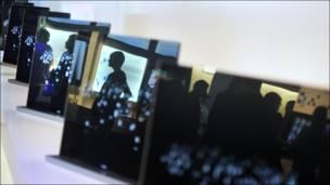La imagen de los visitantes a la feria IFA, en Berlin, se reflejan en la pantalla de algunos de los televisores en exhibición.