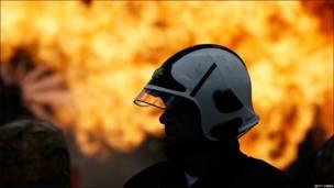 La silueta de un bombero se recorta contra una pared de fuego, durante la realización del simulacro de evacuación más grande en la historia del Reino Unido.