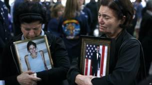 Dos mujeres sostienen fotos de sus familiares fallecidos el 11S