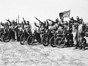 مجموعة من عناصر الحرس الثوري الايراني تلوح باشارة النصر. كان هؤلاء الجنود بدراجاتهم النارية وقاذفات القنابل روسية الصنع يشكلون قوة سريعة وفعالة ضد الدروع العراقية