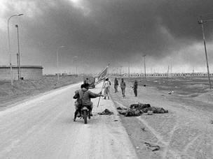 جنود ايرانيون على دراجة نارية يمرون بجانب جثث جنود عراقيين في قضاء الفاو في اقصى جنوب العراق في اوائل فبراير شباط 1986 خلال الحرب الايرانية العراقية